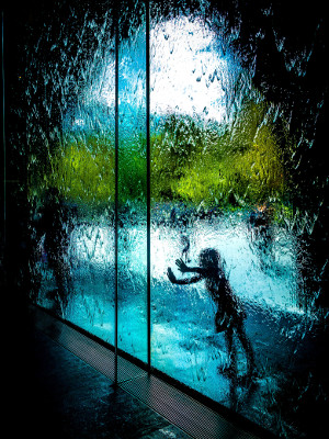 Girl pushing on large glass door