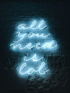 "Neon sign on wall ""all you need is lol"""